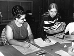 Poll workers sign voters in by Herman Seid