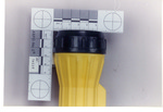 Weapon 43. Closeup of lens of yellow plastic flashlight, side view