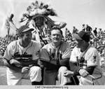 Hank Greenberg and Joe Gordon of the Cleveland Indians, with Johnny Mize of the New York Giants, pose in front of Chief White Mountain Lion during a spring training game by Acme Newspictures